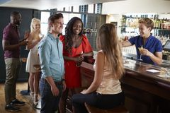 Group Of Young Friends Relaxing In Bar Standing At Counter stock photography