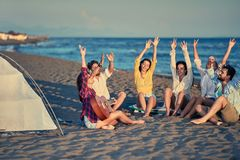 Young friends relaxing with playing guitar and sing a song on se. Group of young friends relaxing with playing guitar and sing a song on sea beach Royalty Free Stock Image