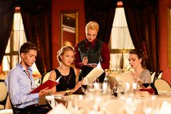Group of young friends in restaurant. Group of young friends with menus choosing in a luxury restaurant royalty free stock photography