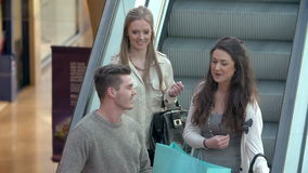 Group Of Young Friends Riding Escaltor In Shopping Mall stock video footage