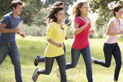 Group Of Young Friends Running Through Countryside Royalty Free Stock Photos