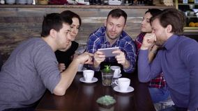 Group of young friends sitting at the restaurant together talking to each other and using digital gadget. Three handsome stock video