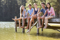 Group Of Young Friends Sitting On Wooden Jetty Looking Out Over Lake Royalty Free Stock Photography