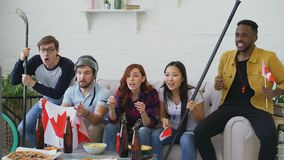Group of young friends sports fans with Canadian national flags watching sport championship on TV together cheering up. Favourite team at home indoors stock footage