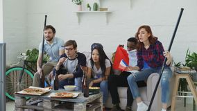 Group of young friends sports fans with French national flags watching sport championship on TV together cheering up. Favourite team at home indoors stock footage