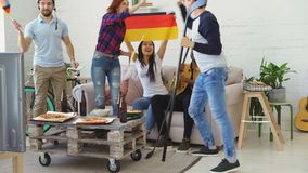 Group of young friends sports fans with German national flags watching sport championship on TV together and happy about. Winning favourite team at home indoors stock video