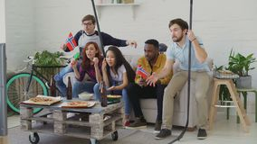Group of young friends sports fans with Norwegian national flags watching sport championship on TV together and happy. About winning favourite team at home stock footage