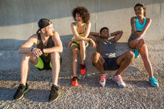 Group of young friends in sportswear resting and talking outdoors Stock Photo