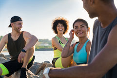 Group of young friends in sportswear talking while resting. Outdoors after jogging stock images