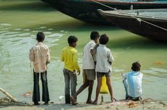 Boys at the Riverbank. A group of young friends stand together and look out over the Ganges River, Varanasi, India Stock Photo