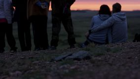 Group of young friends standing together and looking at sunset. Rear view of young people admiring a view. Group of stock photos