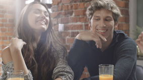 Group of young friends talking around a table with healthy orange drinks in a leisure day in modern loft interior. stock video footage