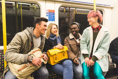 Group of young friends travelling together by tube. In London. Mixed race group, two men and two women, wearing colourful warm clothes and having fun together stock photo