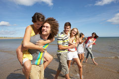 Group Of Young Friends Walking. Along Summer Shoreline Royalty Free Stock Images