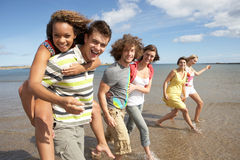 Group Of Young Friends Walking. Along Summer Shoreline Stock Images