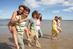 Group Of Young Friends Walking Along. Summer Shoreline Stock Photo