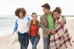Group Of Young Friends Walking Along Autumn. Shoreline Royalty Free Stock Photography