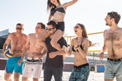 Group of young friends walking on the beach volleyball court. stock photos