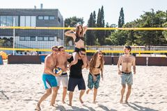 Group of young friends walking on the beach volleyball court. royalty free stock photography