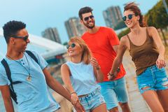 Group of young friends walking through the city. Group of young friends walking through the city by the river talking and having fun stock photography