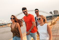 Group of young friends walking through the city. Group of young friends walking through the city by the river talking and having fun stock image