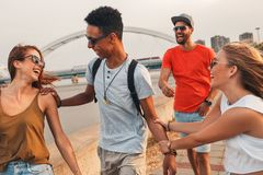 Group of young friends walking through the city. Group of young friends walking through the city by the river talking and having fun stock photo