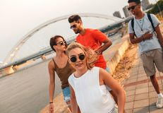 Group of young friends walking through the city. Group of young friends walking through the city by the river talking and having fun stock images