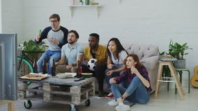 Group of young friends watching football game on TV together eating snacks and drinking beer at home. Men are happy with. Group of young friends watching stock video footage
