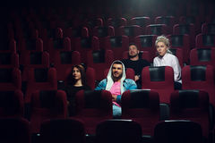 Group of young friends watching movie in theater Stock Photography