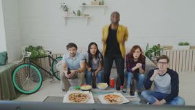 Group of young friends watching olympic games match on TV together eating snacks and drinking beer. African man is happy. Group of young friends watching olympic stock footage