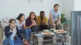 Group of young friends watching sports match on TV together eating snacks and drinking beer at home. Some of them happy. Group of young friends watching olympic stock footage