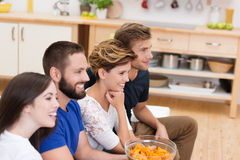 Group of young friends watching television. Sitting together in a row on the sofa with focus to the centre couple holding a bowl of snacks royalty free stock image
