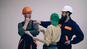 Group of young, funny and hard working builders isolated on white. Male and female builders in helmets standing on white stock footage