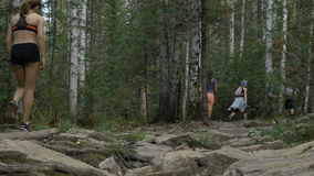 Group of young girls athletes running along a stone trail in forest stock video footage