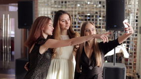 A group of young girls in beautiful dresses doing selfie at a party. stock video footage