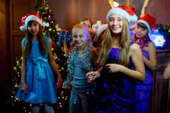 Group of young girls celebrating Christmas. First plan. Group of cheerful young girls celebrating Christmas near the Christmas tree with lights. Disco. First Stock Photography