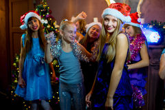 Group of young girls celebrating Christmas. First plan. Group of cheerful young girls celebrating Christmas near the Christmas tree with lights. Disco. First Royalty Free Stock Image