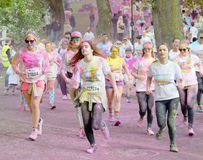 Group of young girls covered with color powder running Royalty Free Stock Photo