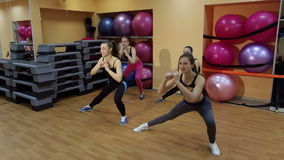 Group of young girls doing exercise for legs in the gym. stock video