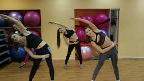 Group of young girls doing stretching exercise in gym. stock footage