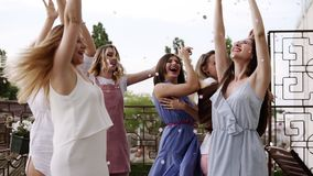 Group of young girls dressed in casual partying outdoors on terrace silver confetti in the air at daytime during their