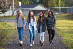 Group of young girls holding hands and laughing while walking on Royalty Free Stock Images