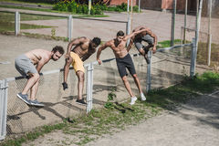Young handsome men jumping over fence on court Stock Photography