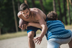 Young handsome men playing football on court Stock Photography