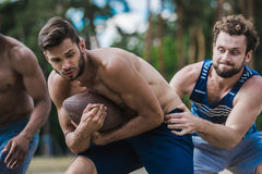 Young handsome men playing football on court Royalty Free Stock Image