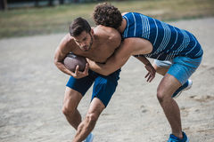 Young handsome men playing football on court Royalty Free Stock Photos