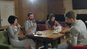 Group of young happy friends having fun at karaoke, singing, taking selfie, drinking tea stock video footage