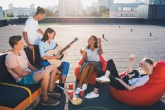 Friends having party on roof. Group of young happy friends having party on roof with acoustic guitar Stock Image