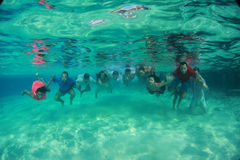 Group of young happy friends people swim diving underwater with bridal couple bride and groom near them wedding Royalty Free Stock Photos