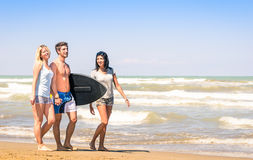Group of young happy friends with surfboard at the beach Royalty Free Stock Photography